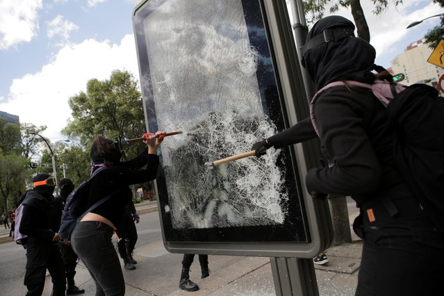 Demonstrators smash a billboard during a protest in support of Victoria Salazar, a Salvadoran woman who died after a Mexican female police officer was seen in a video kneeling on her back, in Mexico City, Mexico on April 2, 2021. (Photo by Raquel Cunha/Reuters)
