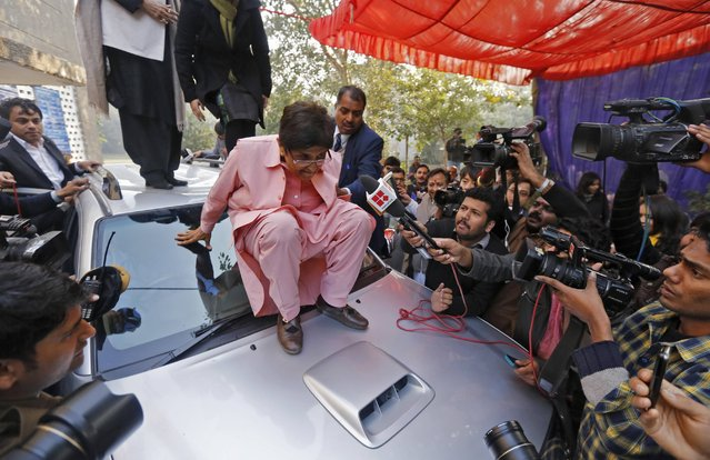 India's ruling Bharatiya Janata Party (BJP) chief ministerial candidate for Delhi Kiran Bedi (C), who cast her vote at a polling station, prepares to step down from the bonnet of the car after greeting her supporters during the state assembly election in New Delhi February 7, 2015. (Photo by Adnan Abidi/Reuters)