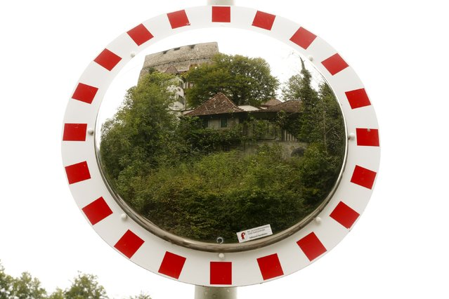 A former infantry bunker camouflaged as a medieval house is reflected in a mirror in Duggingen, Switzerland August 19, 2015. With the threat of foreign invasion a thing of the past, thousands of military bunkers and fortresses in Switzerland have been put to commercial use, from hotels to data centres, museums to cheese factories. (Photo by Arnd Wiegmann/Reuters)