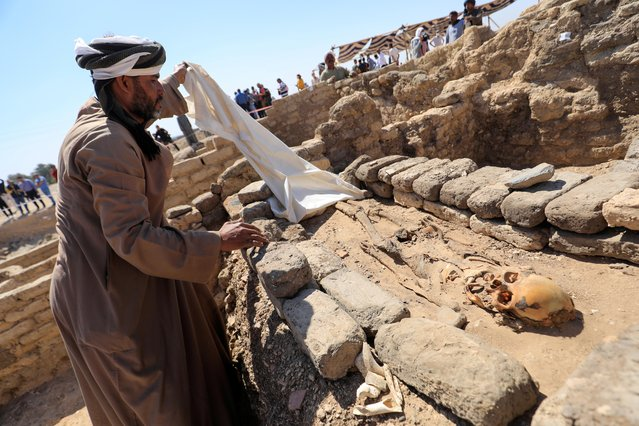 """A man looks at skeletal human remains at the site of the """"Lost Golden City"""", which was recently discovered by archaeologists, in the West Bank of Luxor, Upper Egypt, April 10, 2021. (Photo by Amr Abdallah Dalsh/Reuters)"""