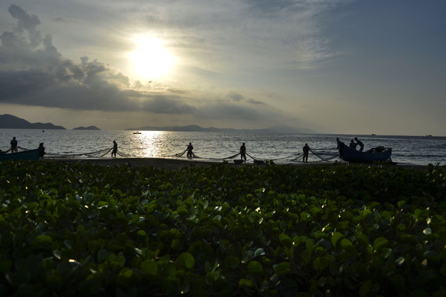 Fishermen pull their nets after fishing during sunset at a beach in Banda Aceh on April 8, 2021. (Photo by Chaideer Mahyuddin/AFP Photo)
