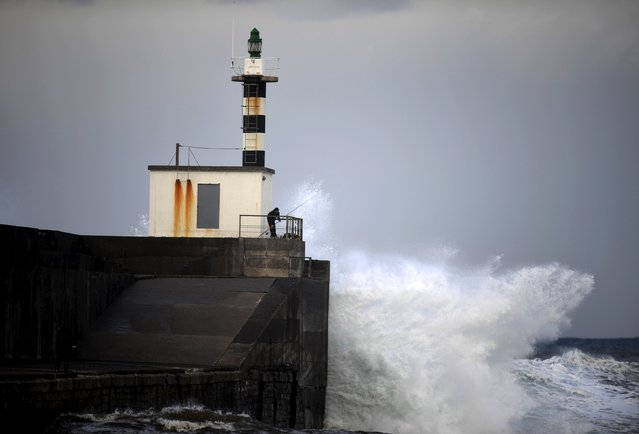 A man fishes as large waves from a storm crash against a lighthouse at the port of San Esteban de Pravia in the northern Spanish region of Asturias, January 11, 2016. (Photo by Eloy Alonso/Reuters)