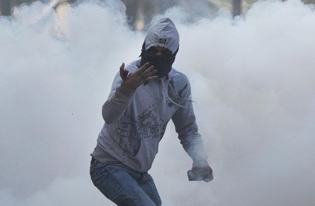 A Kashmiri Muslim masked protester checks his injuries after a tear gas shell, fired by Indian police forces, exploded in his hand during a protest in Srinagar, Indian controlled Kashmir, Friday, January 15, 2016. Police fired teargas and rubber bullets to disperse Kashmiris who gathered after Friday afternoon prayers to protest against Indian control over a part of the disputed region. (Photo by Dar Yasin/AP Photo)