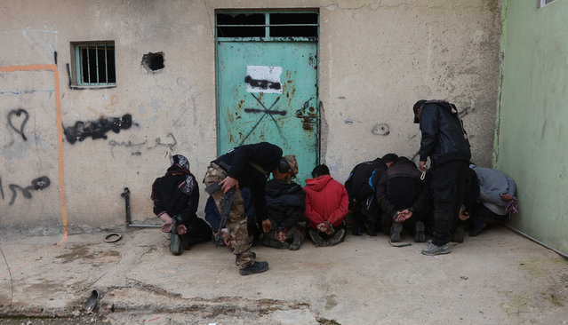 Handcuffed men, who according to the Iraqi security forces are suspected Islamic State militants, are seen in Eelam neighborhood east of Mosul, Iraq, December 8, 2016. (Photo by Reuters/Stringer)