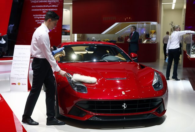 An employee dusts off a Ferrari F12berlinetta during the first press day ahead of the 85th International Motor Show in Geneva March 3, 2015.  REUTERS/Arnd Wiegmann