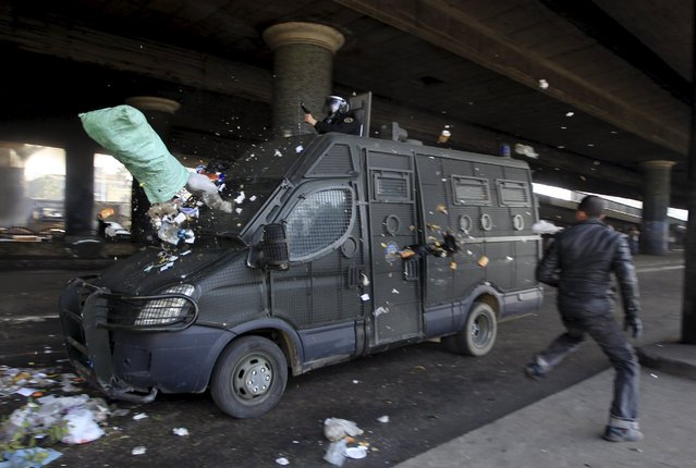 A protester runs next to a police vehicle after throwing a bag of trash at it during a demonstration in Cairo January 28, 2011. (Photo by Goran Tomasevic/Reuters)