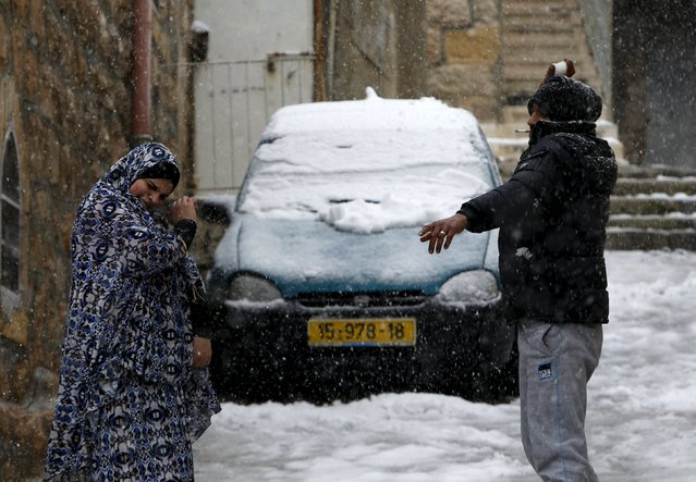 A Palestinian throws snow at his wife during a snow storm in West Bank old city of Hebron, January 26, 2016. (Photo by Mussa Qawasma/Reuters)