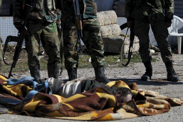 Forces loyal to Syria's President Bashar al-Assad stand near the body of who they said was a rebel fighter, in the town of Rabiya after they recaptured the rebel-held town in coastal Latakia province, Syria January 27, 2016. Syrian pro-government forces recaptured a key rebel-held town in coastal Latakia province on Sunday, building on battlefield advances in the area ahead of planned peace talks this week in Geneva between Damascus and Syria's opposition. Picture taken during a tour organised by the government. (Photo by Omar Sanadiki/Reuters)