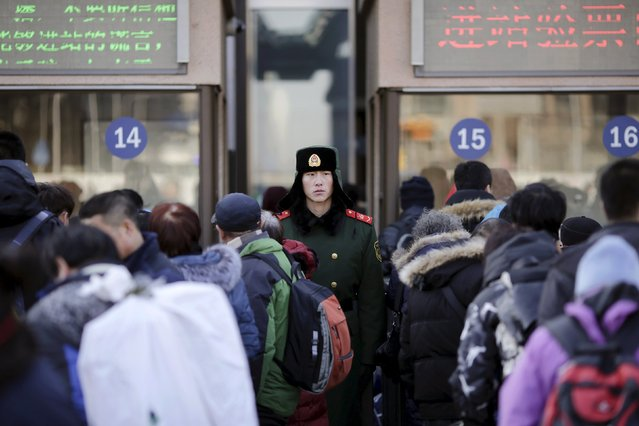 A paramilitary policemen looks at passengers arriving at the Beijing Railway Station as migration for the annual Spring Festival begins in central Beijing, January 24, 2016. (Photo by Damir Sagolj/Reuters)