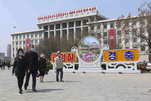 People walk in a street near the Arch of Triumph on the Day of the Sun, the birth anniversary of late leader Kim Il Sung, in Pyongyang, North Korea Thursday, April 15, 2021. (Photo by Cha Song Ho/AP Photo)
