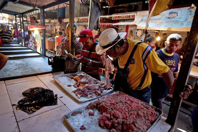 In this August 19, 2018 photo, a customer smells a piece of spoiled meat at a market in Maracaibo, Venezuela. Venezuelans are lining up at one of the country's largest markets to buy spoiled meat. It makes some sick, but at bargain prices, it's the only way they can afford beef. (Photo by Fernando Llano/AP Photo)