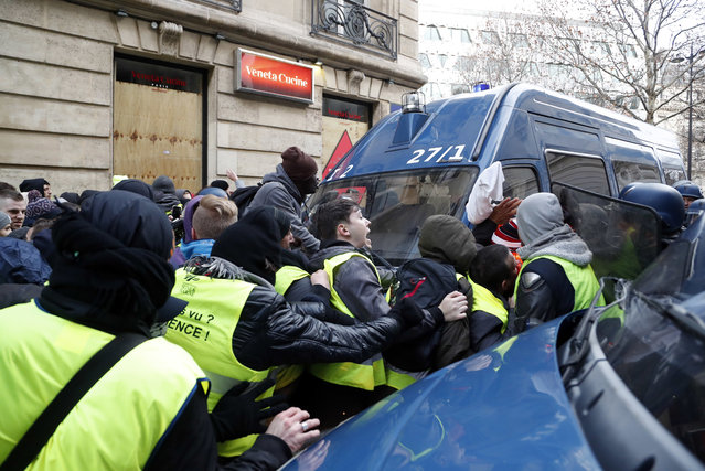 Police officers block demonstrators wearing yellow vests from entering a street in Paris, Saturday, December 8, 2018. (Photo by Thibault Camus/AP Photo)