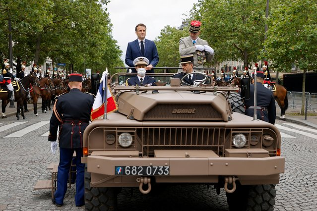 French President Emmanuel Macron and French Armies Chief of Staff General Francois Lecointre stand in the command car prior to review troops during the annual Bastille Day military parade on the Champs-Elysees avenue in Paris on July 14, 2021. (Photo by Ludovic Marin/Pool via AFP Photo)