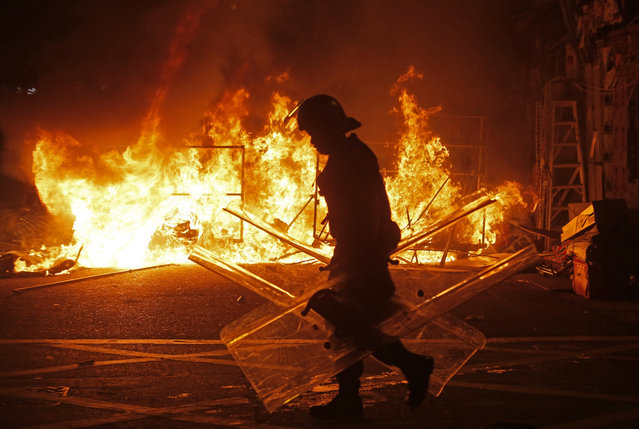 A police officer walks past fire set by rioters in Mong Kok district of Hong Kong, Tuesday, February 9, 2016. (Photo by Vincent Yu/AP Photo)
