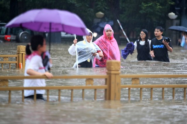 People walk through floodwaters along a street in Zhengzhou in central China's Henan Province, Tuesday, July 20, 2021. (Photo by Chinatopix via AP Photo)