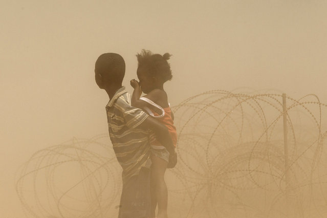Children are engulfed in dust as a convoy of escorted taxis carrying Muslims, fleeing sectarian violence, arrives at a temporary internally displaced person camp at the airport in Bangui, Central African Republic January 30, 2014. (Photo by Siegfried Modola/Reuters)