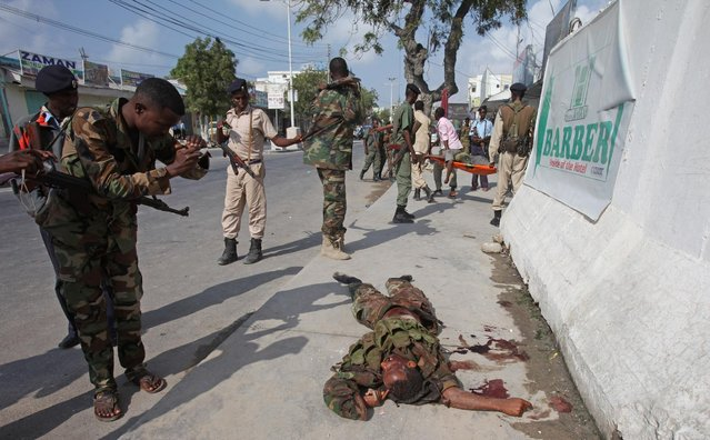 A Somali soldier photographs the body of one of the Al-Shabab militants as it lays on the ground outside the Maka Almukaramaha Hotel, in Mogadishu, Somalia, Saturday, March 28, 2015, who were killed during the second day of siege by Al-Shabab militants . Somali troops on Saturday took full control of a hotel that extremist gunmen stormed and occupied for more than 12 hours following a suicide bombing. (Photo by Farah Abdi Warsameh/AP Photo)
