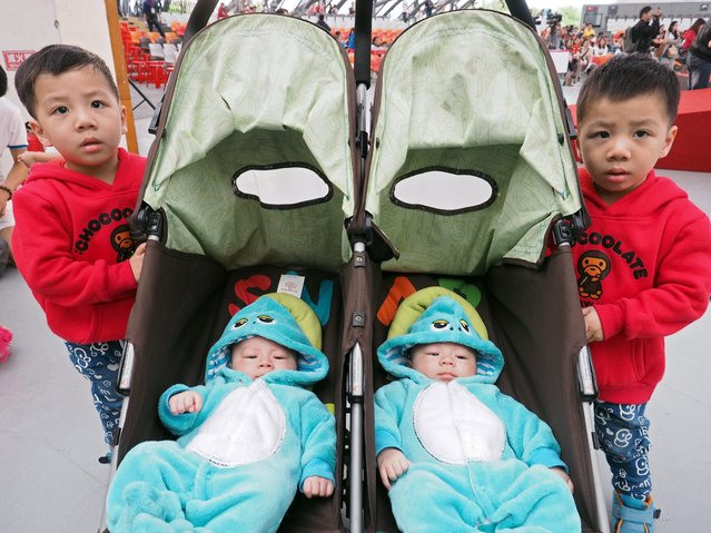 Two sets of twin brothers from one family, respectively four months old and three year old, attend the thrid Twins Reunion in Taipei, Taiwan, 21 March 2015. The boys' mother Pai Ya-chi said that members of her family have been having twins for three generations. Some 400 sets of twins and triplets attended the event which featured songs and and dance by twins, selection of the most look-alike twins and raffle. (Photo by David Chang/EPA)