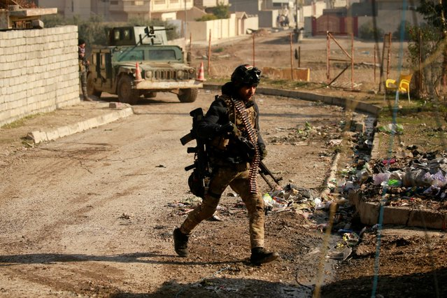 A member of Iraqi rapid response forces carries his weapon during a battle with Islamic State militants in the Mithaq district of eastern Mosul, Iraq, January 3, 2017. (Photo by Thaier Al-Sudani/Reuters)