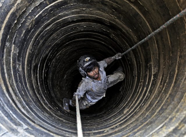 Nepalese worker Deepak Kumal, 27, hangs on a rope as he digs in well for a water source in Kathmandu, Nepal, 22 March 2015. On the backdrop of rapid urban population growth, industrialization and uncertainties caused by climate change, Kathmandu has been facing water crises during winter and spring seasons. International World Water Day is marked on 22 March annually focusing importance of freshwater. (Photo by Narendra Shrestha/EPA)