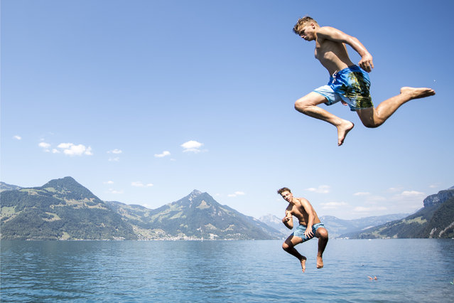 Young men jump into Lake Lucerne in Beckenried, Canton Nidwalden, Switzerland, on Monday, July 30, 2018. The European weather forecast predicts high temperatures for the next few days. (Photo by Urs Flueeler/KEYSTONE via AP Photo)