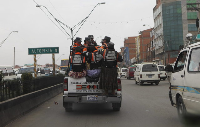 In this December 13, 2013 photo, Aymara traffic policewomen are transported to a checkpoint to help control and direct traffic in El Alto, Bolivia. (Photo by Juan Karita/AP Photo)