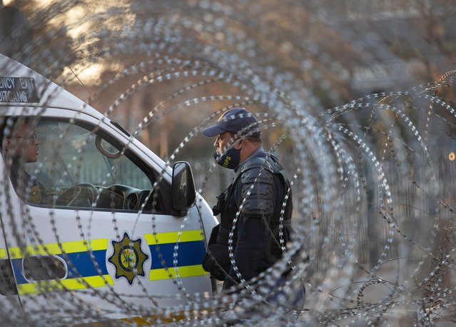 South African Police (SAPS) personal guards the High Court as security measures remain high during the court case of former South African President Jacob Zuma, in Pietermaritzburg, South Africa, 10 August 2021. Former President Zuma did not appear in person as he is in hospital and the case continued via a virtual sitting. (Photo by Kim Ludbrook/EPA/EFE)