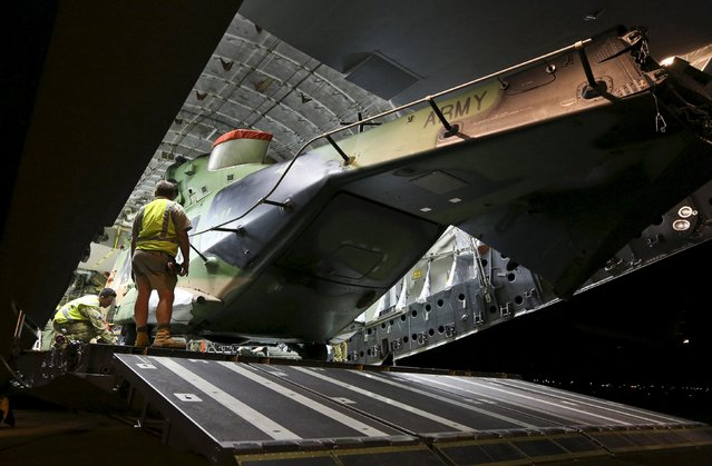 Australian Air Force and Army personnel load a Multi Role Helicopter (MRH 90) onto an Australian Air Force C-17 aircraft before departing from RAAF Base Townsville in Australia, en route to assist in Cyclone Winston-ravaged Fiji, in this handout image supplied by the Australian Defence Force February 23, 2016. (Photo by Reuters/Australian Defence Force)