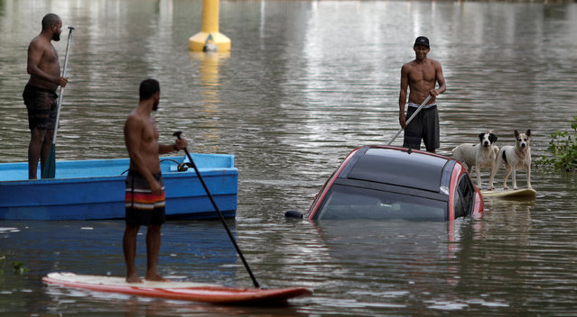 Residents try to rescue a car pushed by the floods to a channel after heavy rains in Barra da Tijuca neighbourhood in Rio de Janeiro, Brazil February 7, 2019. (Photo by Ricardo Moraes/Reuters)