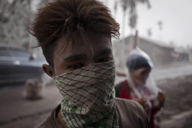 An ash covered man wears a mask as his village was hit by ash from eruption of Mount Sinabung in Payung village on January 8, 2014 in Karo District, North Sumatra, Indonesia. (Photo by Ulet Ifansasti/Getty Images)