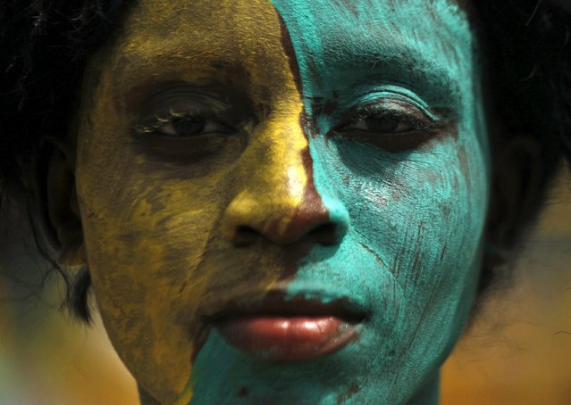 A women with her face painted takes part in a parade during the Popo (Mask) Carnival of Bonoua, in the east of Abidjan, April 18, 2015. (Photo by Luc Gnago/Reuters)