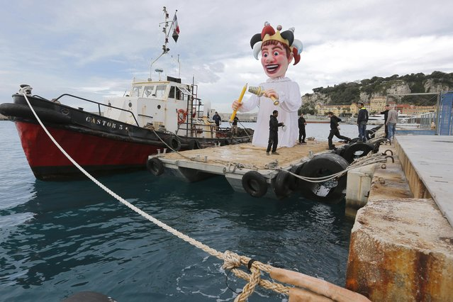 """Workers removed the King of the Nice Carnival 2016's float from a barge in the harbour of Nice, southeastern France, Monday, February 29, 2016. The model had to be burned last night in the bay of Nice during the final parade, but the event was canceled due to bad weather. The Carnival celebrated this year the """"King of Media"""". (Photo by Lionel Cironneau/AP Photo)"""