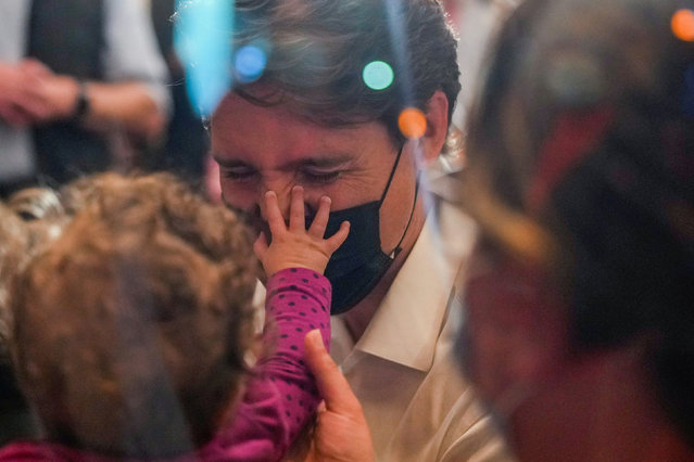 A baby touches Canada's Liberal Prime Minister Justin Trudeau during an election campaign stop at St. Marks restaurant in Longueuil, Quebec Canada on September 15, 2021. (Photo by Carlos Osorio/Reuters)