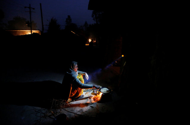A wife of a snake charmer prepares dinner as her daughter holds a torch in Jogi Dera (snake charmers settlement), in the village of Baghpur, in the central state of Uttar Pradesh, India January 17, 2017. (Photo by Adnan Abidi/Reuters)