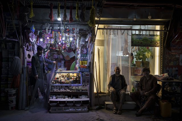 Vendors wait for customers outside their shop in Kabul, Afghanistan, Saturday, September 11, 2021. (Photo by Felipe Dana/AP Photo)