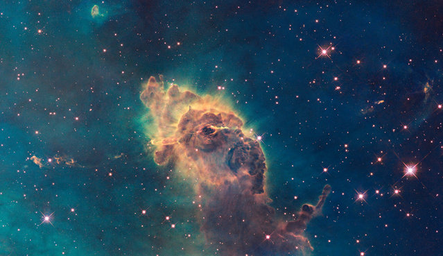This image made by the NASA/ESA Hubble Space Telescope shows the tip of the three-light-year-long pillar in a stellar nursery called the Carina Nebula, located 7500 light-years away from the Earth. Composed of gas and dust, the structure is illuminated by light from hot, massive stars off the top of the image. (Photo by NASA/ESA/Hubble SM4 ERO Team via AP Photo)