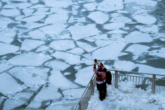 A pedestrian stops to take a photo by Chicago River, as bitter cold phenomenon called the polar vortex has descended on much of the central and eastern United States, in Chicago, Illinois, U.S., January 29, 2019. (Photo by Pinar Istek/Reuters)