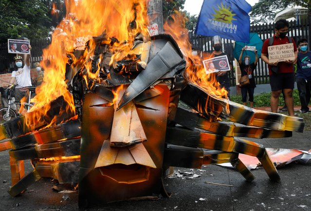 """Protesters burn an effigy of presidential candidate Ferdinand """"Bongbong"""" Marcos Jr., son of the late dictator Ferdinand Marcos, during a rally outside the Commission on Human Rights in Quezon City, Metro Manila, Philippines 06 October 2021. Bongbong Marcos, believed by critics to be an ally of President Rodrigo Duterte, filed on 06 October his candidacy for president in the May 2022 national elections at the Commission on Elections in Manila. (Photo by Rolex dela Pena/EPA/EFE)"""