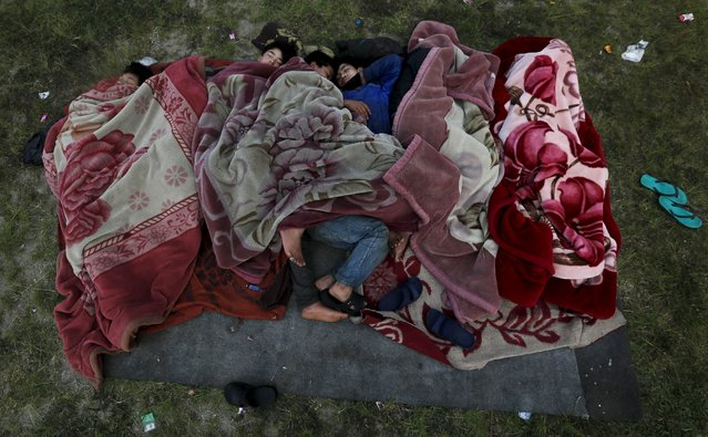 People sleep on the ground in an open area on early morning after an earthquake in Kathmandu, Nepal April 28, 2015. (Photo by Adnan Abidi/Reuters)