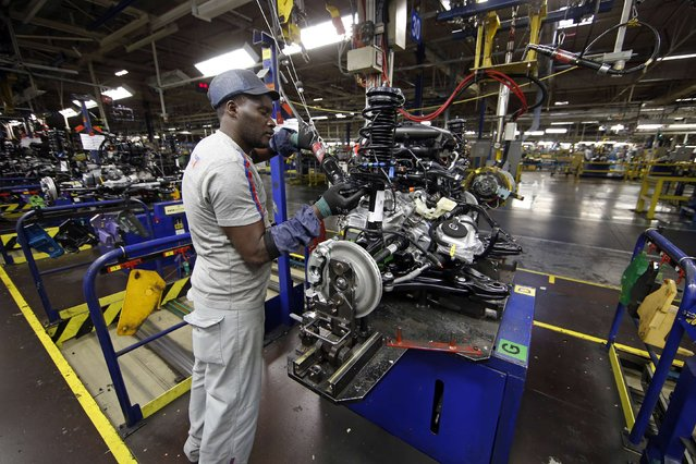 An employee works on an engine on the automobile assembly line of the Peugeot 208, Citroen C3 and DS 3 cars at the PSA Peugeot Citroen plant in Poissy, near Paris, France, April 29, 2015. (Photo by Benoit Tessier/Reuters)