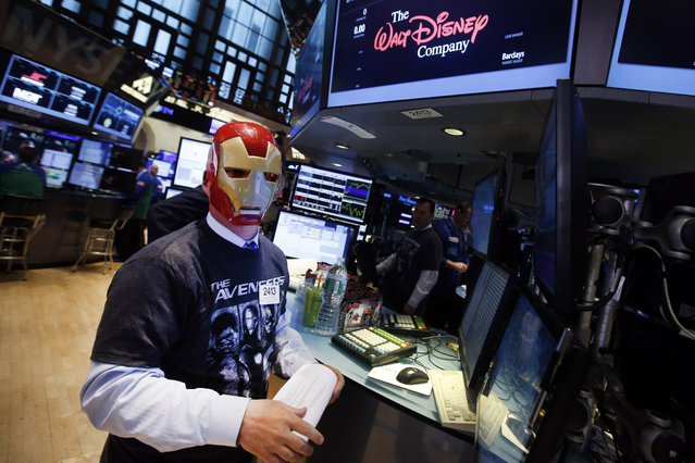 Trader John O'Hara wears an Ironman mask as he works on the floor of the New York Stock Exchange, Monday, April 27, 2015, in New York. Actors Jeremy Renner and Robert Downey Jr. rang the NYSE opening bell Monday with representatives from Marvel Entertainment. (Photo by Jason DeCrow/AP Photo)