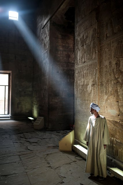 A tour guide waits for tourists inside inside the ancient Temple of Edfu, considered one of the best preserved Egyptian temples, which was built around 3000 years ago, near Aswan, southern Egypt, Friday, May 1, 2015. (Photo by Mosa'ab Elshamy/AP Photo)