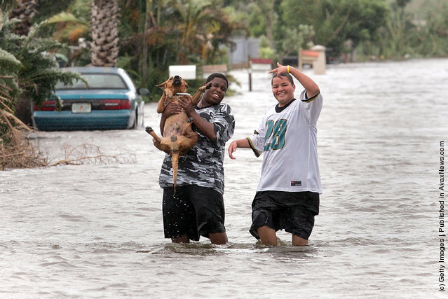 Two youths carry their dog down the flooded street after Hurricane Katrina dumped as much as 15 inches of rain as it passed over this communinty south of Miami August 26, 2005 in Homestead, Florida