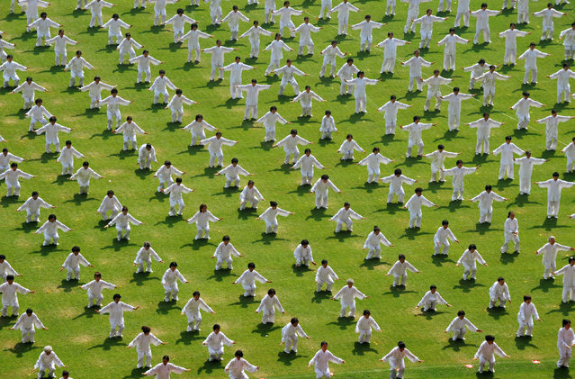 People take part in an attempt to break the Guinness World Record for the largest number of people practicing Taiji in multiple locations, at the Shenyang Olympic Sports Center, to mark the one-year anniversary of the Beijing Olympic Games in Shenyang, Liaoning province August 8, 2009. (Photo by Sheng Li/Reuters)