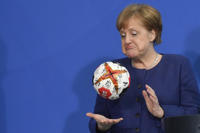 German Chancellor Angela Merkel plays with a handball given to her by the German Handball Federation's president (not in picture) as she received the German national handball team at the Chancellery in Berlin on April 8, 2019. (Photo by John Macdougall/AFP Photo)