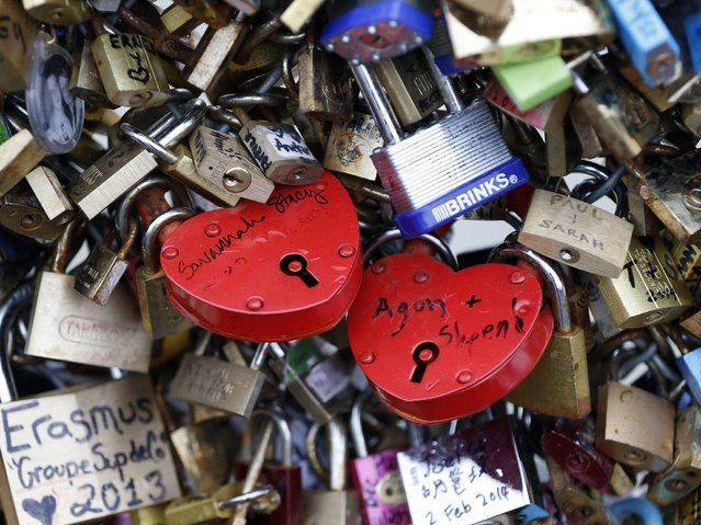 The sweethearts' names or initials are inscribed on the padlock, and its key is thrown away to symbolise unbreakable love. (Photo by Charles Platiau/Reuters)