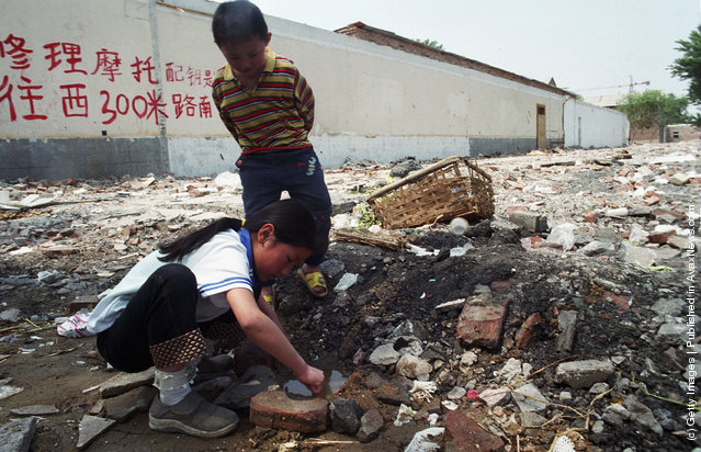 Migrant children from Henan province play in a puddle near a garbage site next to their home in northern Beijing, China