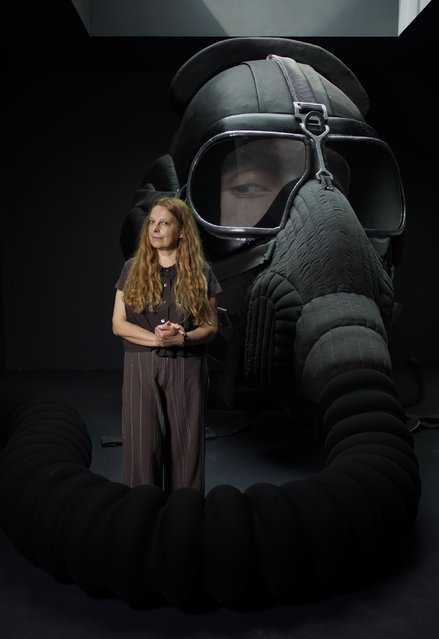 "Russian artist Irina Nakhova poses next to a futuristic sculpture of a head of a pilot inside her installation ""The Green Pavilion"" on display at the Russian pavilion at the 2015 Biennale of Arts in Venice, Italy, Wednesday, May 6, 2015. (Photo by Domenico Stinellis/AP Photo)"