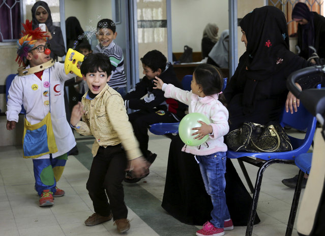In this Thursday, March 17, 2016 photo, 33-year-old Palestinian clown doctor Alaa Miqdad, left, entertains children at Al-Rantisi children's hospital in Gaza City. (Photo by Adel Hana/AP Photo)