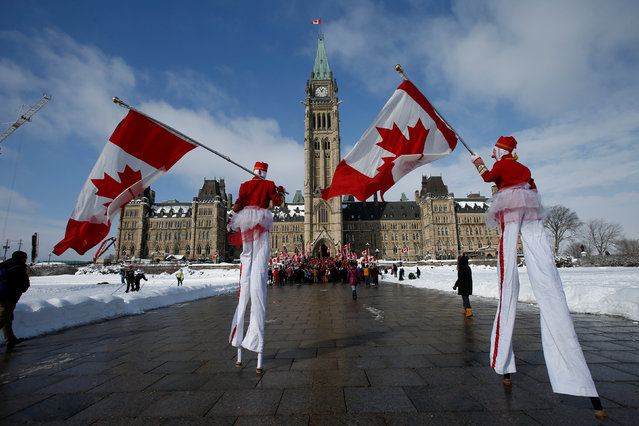 Performers on stilts carry Canadian flags as they arrive for a National Flag of Canada Day ceremony on Parliament Hill in Ottawa, Ontario, Canada February 15, 2017. (Photo by Chris Wattie/Reuters)